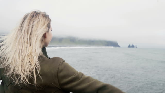 Back view of young blonde woman standing on black beach in iceland. Freedom: tourist rising up hands, hair wave on wind video