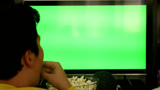 グリーンスクリーンテレビを見てソファに座っている若い男の子のバックビュー - おやつ点の映像素材/bロール