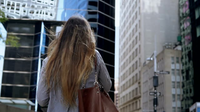 back view of young businesswoman talk on mobile phone and going to work in financial district in new york. slow motion - città diffusa video stock e b–roll