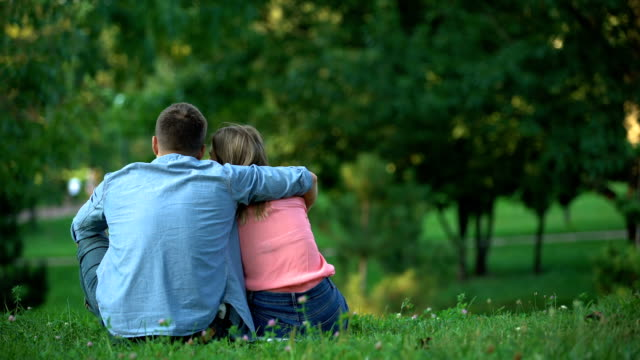 Back view of young couple hugging and sitting on grass at park, togetherness Back view of young couple hugging and sitting on grass at park, togetherness back to back stock videos & royalty-free footage