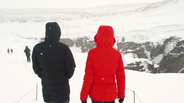 Back view of young couple walking in winter mountain together. Snowy mountain in Iceland