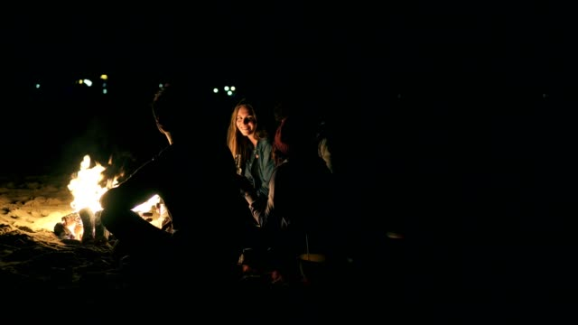 back view of young diverse people sitting together by the fire late at night. cheerful friends talking and having fun together, drinking beer - falò spiaggia video stock e b–roll