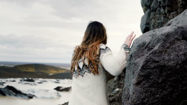 back view of young explorer woman walking through the rocks in mountains, near the vatnajokull ice lagoon in iceland - trekking sul ghiaccio video stock e b–roll