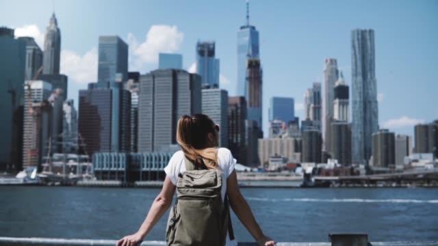 vista sul retro della giovane ragazza turistica felice con zaino e braccia spalancata di gioia nel famoso skyline di manhattan a new york - esplorazione video stock e b–roll