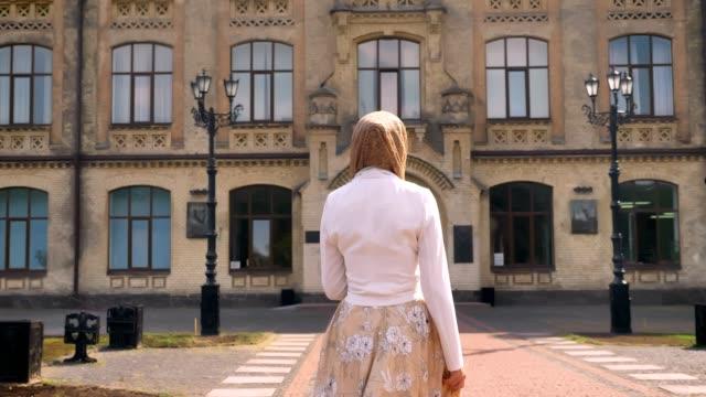 baksidan på ung muslimsk kvinna i hijab gående mot byggnaden, titta runt, solig dag utomhus - endast en ung kvinna bildbanksvideor och videomaterial från bakom kulisserna