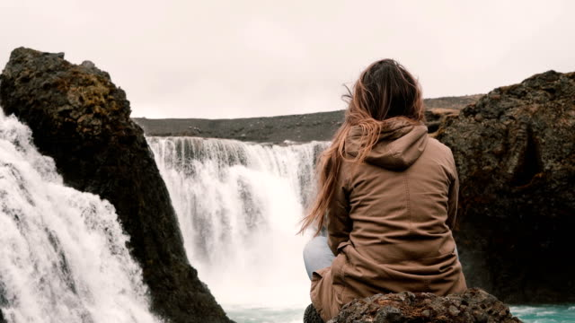 Back view of young pensive woman sitting on a rock alone and looking on powerful waterfall in Iceland video