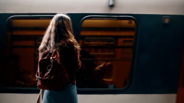 back view of young student woman with backpack standing near in metro near the fast riding train, waiting for a trip - поезд стоковые видео и кадры b-roll