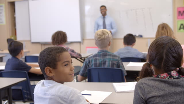 Atrás vista de los jóvenes estudiantes en clase de giro de redondo a la cámara - vídeo