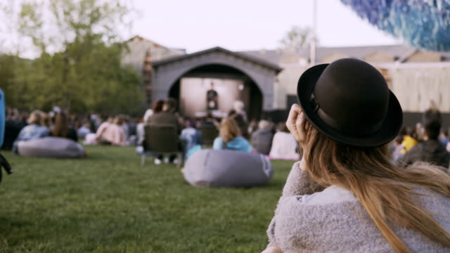 vídeos de stock e filmes b-roll de back view of young stylish woman in hat sitting in bag-chair and looking movie in open-air cinema festival alone - evento