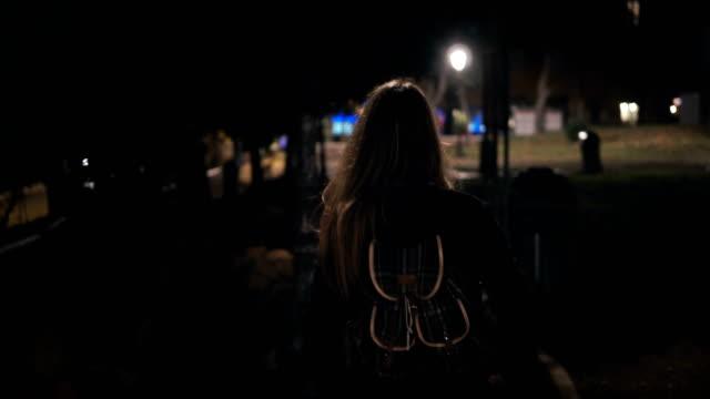 baksidan på ung snygg kvinna gå sent på natten genom den mörka parken. igång på kvällen ensam - fruktan bildbanksvideor och videomaterial från bakom kulisserna