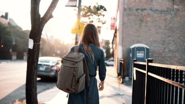 şehir merkezinde vakit yalnız yaz aylarında günbatımı üzerinde yürüyen sırt çantası ile arkadan görünüşü genç şık kadın - sırt çantası stok videoları ve detay görüntü çekimi