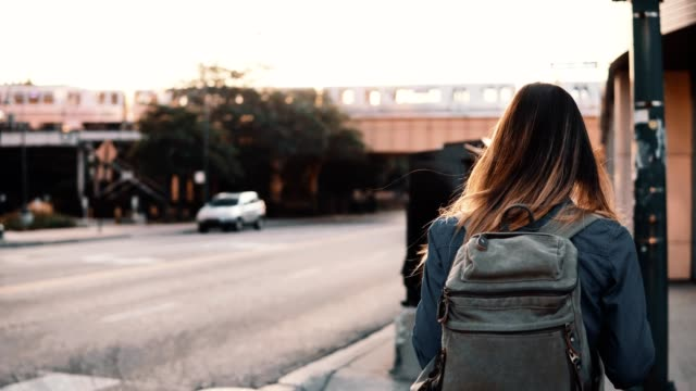 sunset bulvarında yalnız şehir merkezinde yürüyüş, cityscape manzarayı sırt çantası ile arkadan görünüşü genç şık kadın - sırt çantası stok videoları ve detay görüntü çekimi