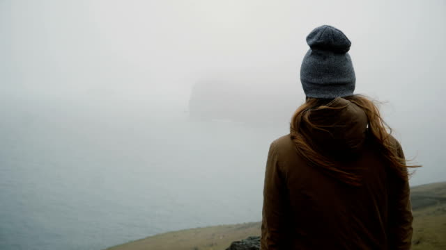 Back view of young woman in hat standing on the shore of the sea and thinking about something, exploring the Iceland video