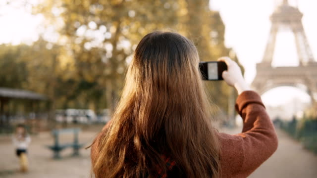 Back view of young woman taking photos on smartphone. Teenager tourist exploring the Eiffel tower in Paris, France