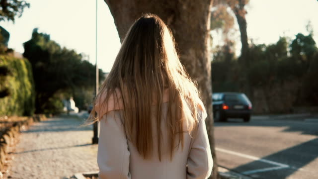 Back view of young woman walking alone at the city centre. Pensive female going near the road in bright sunny day video