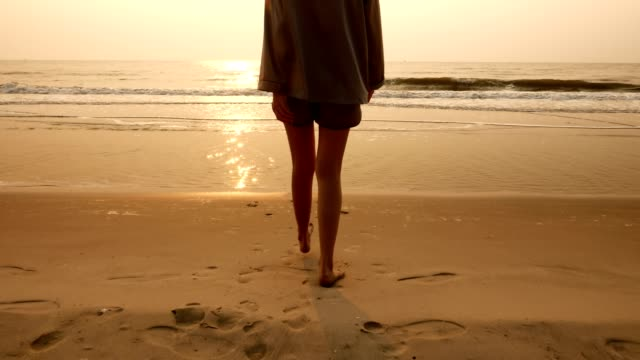 Back view of young woman walking on the beach and enjoying sun over sea in morning