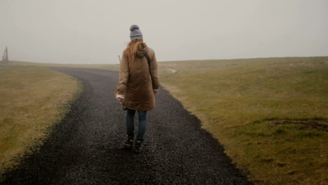 Back view of young woman walking through the field alone. Stylish female exploring the nature of Iceland video