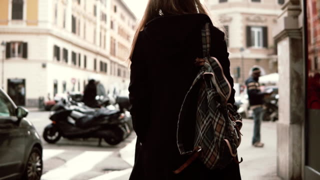 Back view of young woman with backpack walking in the city centre. Girl with backpack spending time alone. Slow motion video