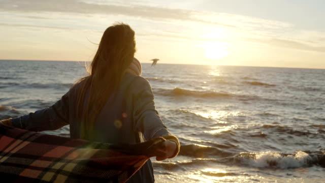 rückansicht der jungen frau mit karomuster, genießen den sonnenuntergang auf der windigen strand mit gestreckten armen. freiheit-konzept - ostsee stock-videos und b-roll-filmmaterial