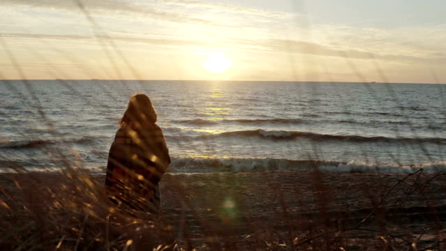 Back view of young woman with plaid on the shore of sea and looking into the distance. Pensive woman at beach on sunset