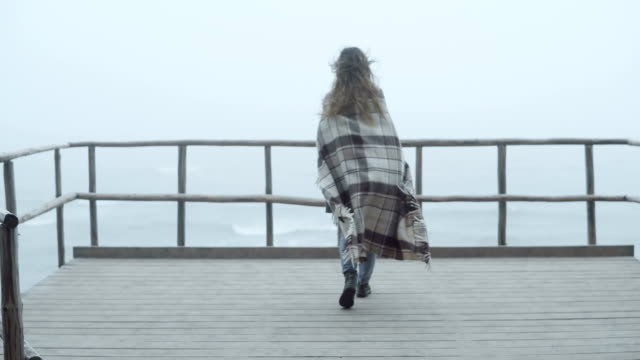 Back view of young woman with plaid standing on the wooden pier and looking afar. Female spends time alone in foggy day video