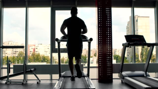 back view on man jogging on treadmill at gym - runner rehab gym video stock e b–roll