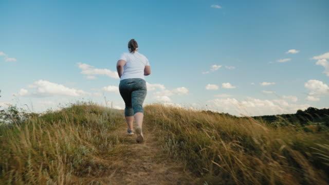back view överviktiga tjejen springer upp för backen - jogging hill bildbanksvideor och videomaterial från bakom kulisserna