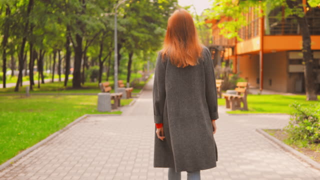 back view redheaded businesswoman enjoy walks outdoors