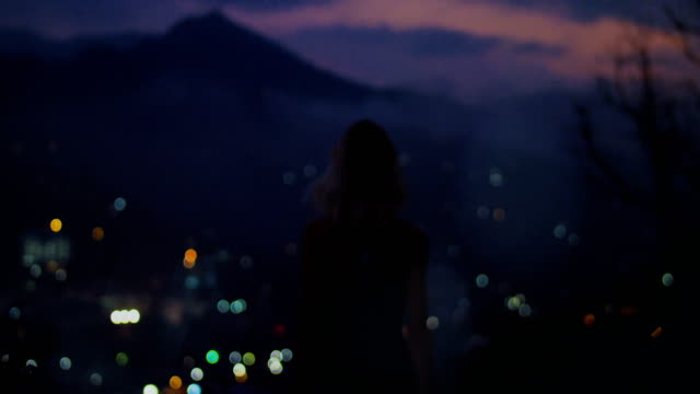 vídeos de stock e filmes b-roll de back view shot of a silhouette of a young woman raising arms with night/ evening city lights and mountain hills in the background. - braços no ar