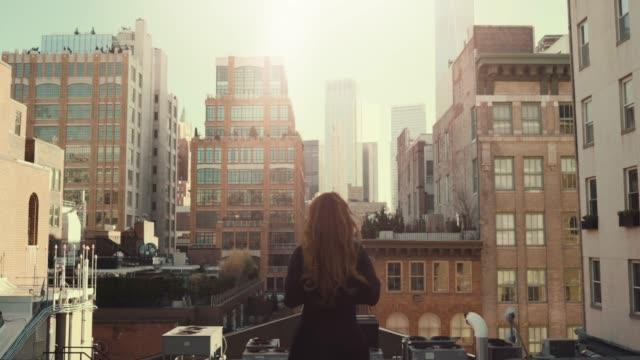 bakifrån skott av vackra röda haired kvinna som står på ett tak. urbana stadsbilden vy över new york city med fantastiska skyskrapor och byggnader. - yttertak bildbanksvideor och videomaterial från bakom kulisserna