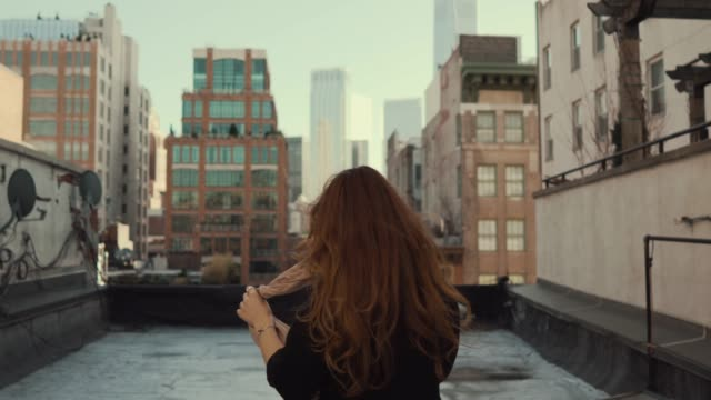 vídeos de stock e filmes b-roll de back view shot of beautiful woman walking on a roof, turning around and smiling wind shuffles her long red hair. urban cityscape view of new york city with great skyscrapers and buildings. - telhado