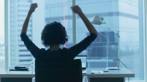 scatto di vista sul retro della bella donna d'affari seduta al suo ufficio, alzando le braccia in una celebrazione di una promozione di lavoro di successo. - capelli castani video stock e b–roll