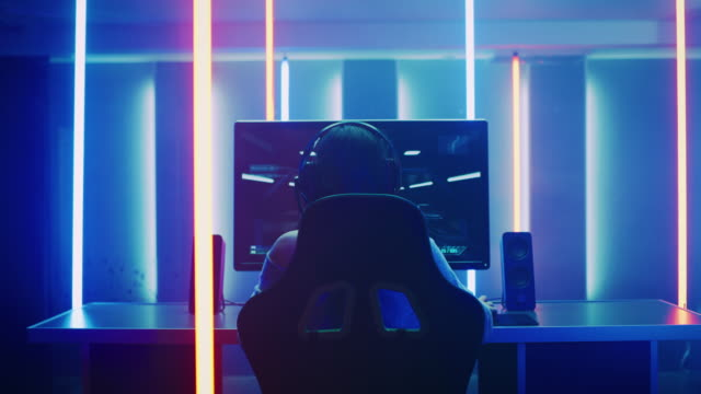 Back View Shot of the Beautiful Professional Gamer Girl Putting on Headset and Starts Playing Online Video Game on Her Personal Computer. Cute Casual Geek Girl. Room Lit by Neon Lamps in Retro Arcade Style.
