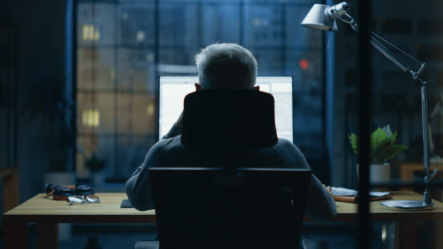 Back view Shot of the Businessman Sitting at His Desk Using Desktop Computer. Stylish Office Studio with Dimmed Light and Big Cityscape Window View