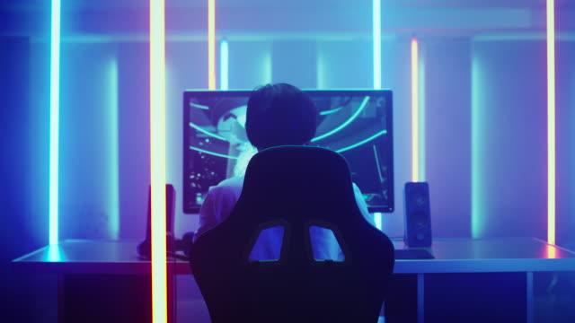 rückansicht schuss das professionelle gamer spielen in first-person-shooter online-videospiel auf seinem persönlichen computer. zimmer, beleuchtet von neonröhren im retro-arcade-stil. online-cyber-e-sport-internet-meisterschaft. - computerspieler stock-videos und b-roll-filmmaterial