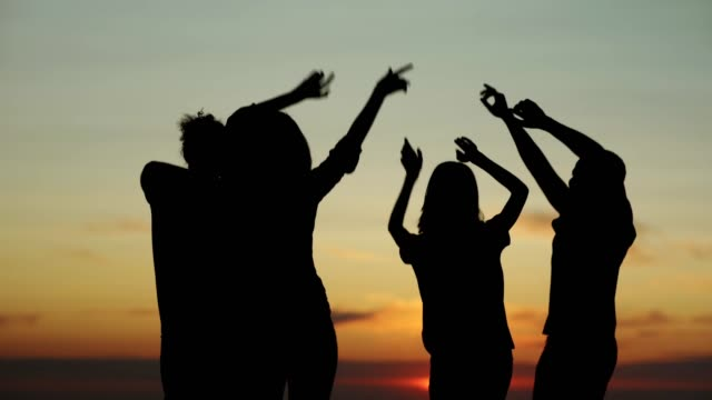 Back view silhouettes of four happy diverse friends dancing by sea with their arms raised up during orange sunset. Young people enjoying summer beach party, three quarter length Back view silhouettes of four happy diverse friends dancing by sea with their arms raised up during orange sunset. Young people enjoying summer beach party, three quarter length beach party stock videos & royalty-free footage