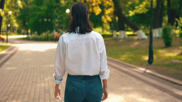 back view trendy female walks on the street unrecognizable woman in casual white shirt and jeans walking in city park summer season slow motion behind stock videos & royalty-free footage