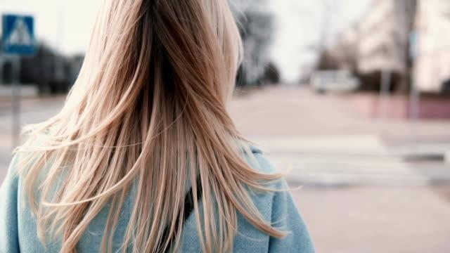 görünüm kadın yürüyen uzun sarı saçlı geri. mavi paltolu güzel uzun sarı saçlar ile iş kadını. ağır çekim - sarı saç stok videoları ve detay görüntü çekimi
