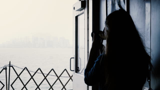 Back view young female journalist on board of a ferry to Manhattan Island taking photos with a professional camera video