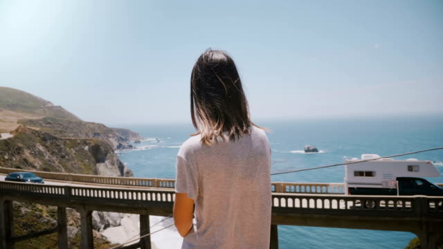 Back view young peaceful local woman watching beautiful scenery of cars moving over iconic Bixby Canyon bridge, Big Sur. video