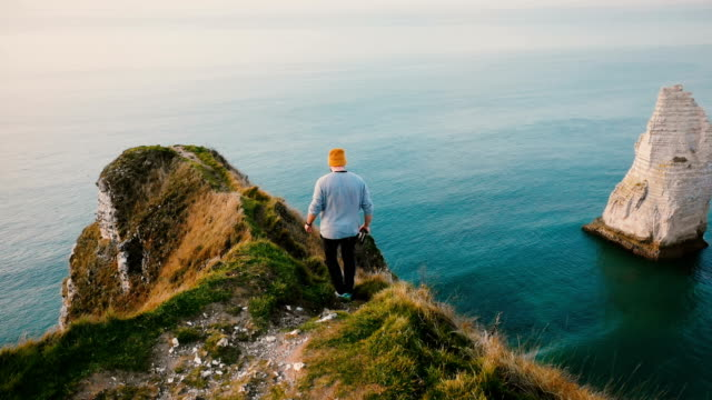 Back view young tourist man walking along dangerous path on top of Normandy coast cliff to enjoy epic seascape scenery.