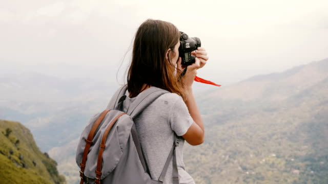 Back view young tourist woman with backpack and camera takes photos of epic breathtaking mountain view in Sri Lanka. video