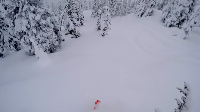 Backcountry skier descends from a snowy ridge in mountains video