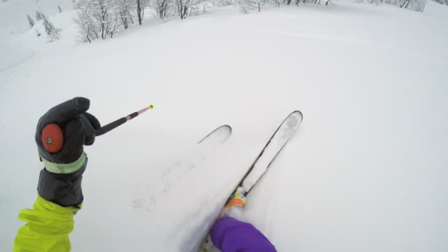pov backcountry skier skiing down the mountain slope in a remote area - sci freestyle video stock e b–roll