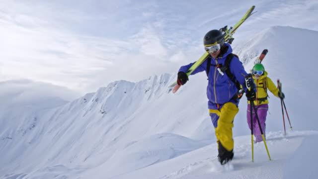 pan backcountry skiers walking on a snowy mountain ridge - sci sci e snowboard video stock e b–roll