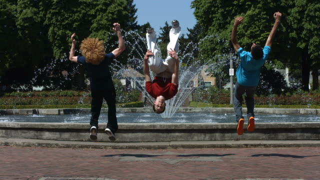 Backflips in front of fountain, slow motion video