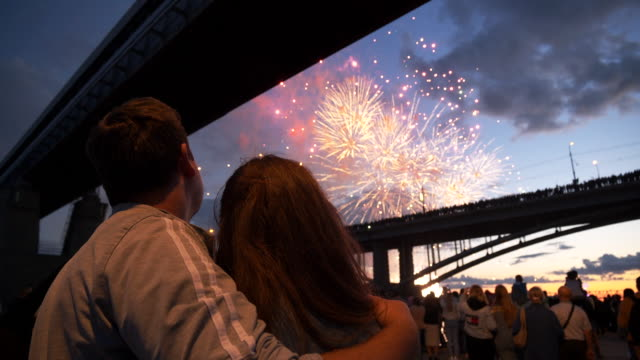 Background beautiful bright firework man and woman standing nearby enjoy show 4K