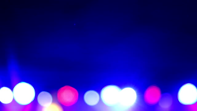 Background of the dance is blurred people dancing in a nightclub. Blue and purple colors