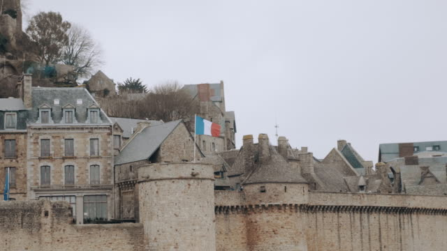 Background shot of French flag waving on majestic ancient Mont Saint Michel, famous island fortress town slow motion.