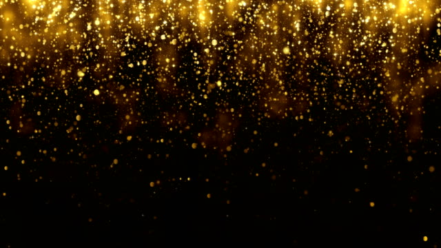 Video Background with falling golden glitter particles. Falling gold confetti with magic light. Beautiful light background. Seamless loop